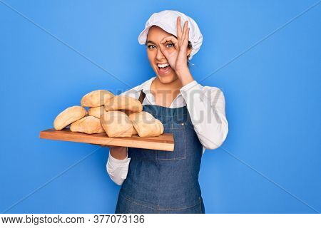 Young beautiful blonde baker woman with blue eyes holding tray with homemade fresh bread with happy face smiling doing ok sign with hand on eye looking through fingers
