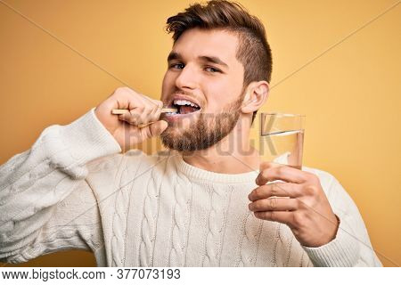 Young handsome caucasian man brushing his teeth using tooth brush, oral paste and glassof water, cleaning teeth and tongue as healthy health care morning routine