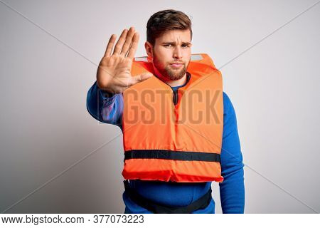 Young blond tourist man with beard and blue eyes wearing lifejacket over white background doing stop sing with palm of the hand. Warning expression with negative and serious gesture on the face.