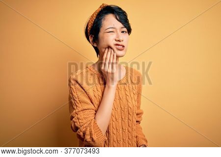 Young beautiful asian women wearing casual sweater and diadem standing over yellow background touching mouth with hand with painful expression because of toothache or dental illness on teeth. Dentist
