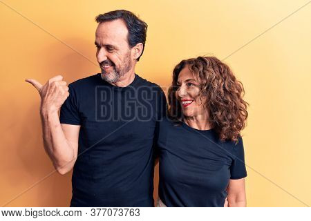 Middle age beautiful couple wearing t-shirt standing over isolated yellow background pointing thumb up to the side smiling happy with open mouth