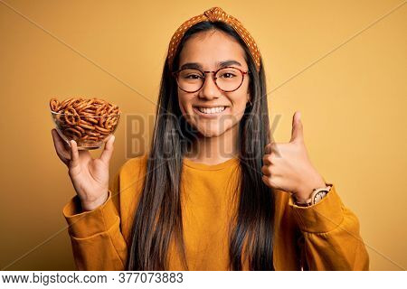 Young beautiful asian woman holding bowl with german baked pretzels over yellow background happy with big smile doing ok sign, thumb up with fingers, excellent sign