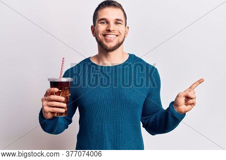 Young handsome man dirnking cola refreshment beverage smiling happy pointing with hand and finger to the side