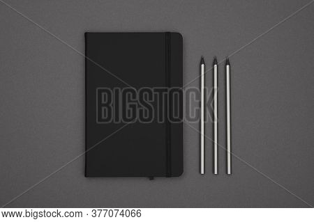 Close Up One Closed Black Leather Cover Notebook And Pencils Over Grey Paper Background, Flat Lay, D