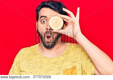 Young hispanic man holding lemon scared and amazed with open mouth for surprise, disbelief face