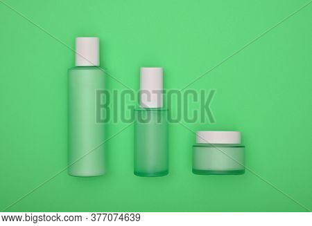 Close Up Set Of Three Cosmetic Skin Care Cream, Lotion And Tonic Bottles Over Green Background, Elev
