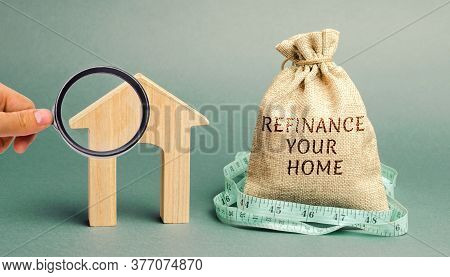 Money Bag With The Words Refinance Your Home And Miniature House. Real Estate Concept. Business And