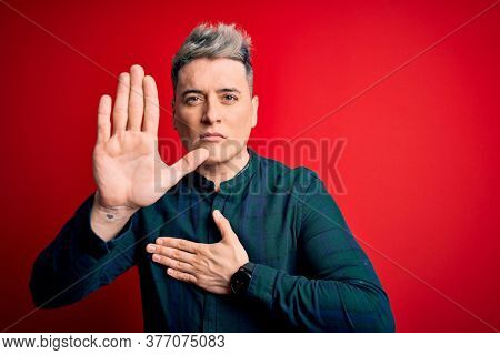 Young handsome modern man wearing elegant green shirt over red isolated background Swearing with hand on chest and open palm, making a loyalty promise oath