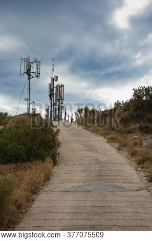 Telecommunications 4g 5g Towers On Top Of A Hill Near Town Of Primosten, Croatia. Small Path Leading