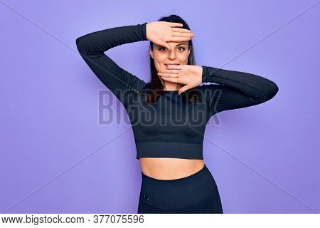 Young beautiful brunette sporty woman wearing casual sportswear over purple background Smiling cheerful playing peek a boo with hands showing face. Surprised and exited