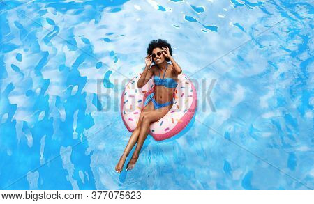 Summer Time Concept. Beautiful Black Woman In Blue Bikini Swimming On Inflatable Ring At Pool During