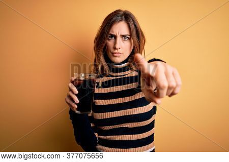 Young beautiful brunette woman drinking glass with cola refreshment using straw pointing with finger to the camera and to you, hand sign, positive and confident gesture from the front