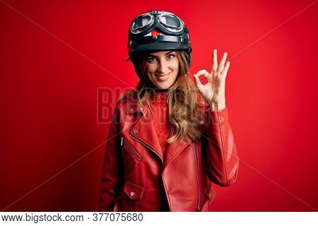 Young beautiful brunette motrocyclist woman wearing moto helmet over red background smiling positive doing ok sign with hand and fingers. Successful expression.