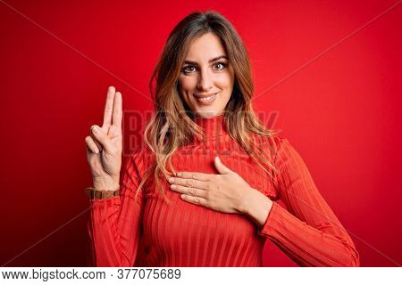 Young beautiful brunette woman wearing casual turtleneck sweater over red background smiling swearing with hand on chest and fingers up, making a loyalty promise oath