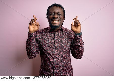 Young handsome african american man wearing casual shirt standing over pink background gesturing finger crossed smiling with hope and eyes closed. Luck and superstitious concept.