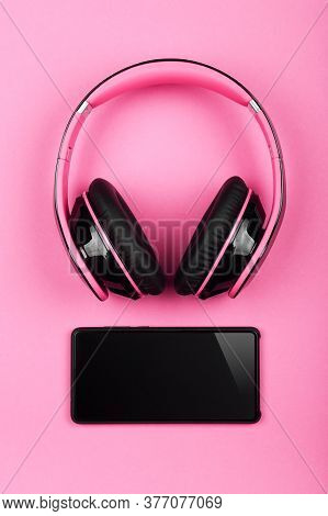 Close Up Modern Wireless Plastic Pink Headphones With Big Cushions And Black Mobile Phone On Table,