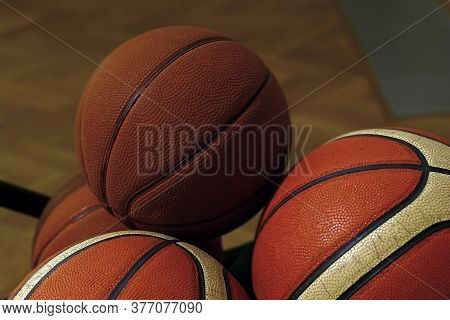 Close Up Group Of Several Old Vintage Basketball Balls On Floor, Low Angle Side View