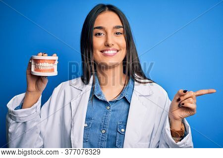Young beautiful brunette dentist woman wearing coat holding plastic teeth prosthesis very happy pointing with hand and finger to the side