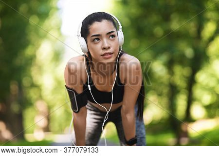 Best Playlist For Running. Tired Asian Female Athlete Resting After Jogging Outdoors And Listening M