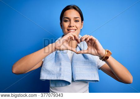Young beautiful brunette sportswoman wearing towel doing exercise over blue background smiling in love showing heart symbol and shape with hands. Romantic concept.