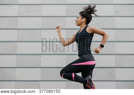 Jogging With Favorite Music. African American Girl In Sport Uniform With Fitness Tracker, Runs On Br