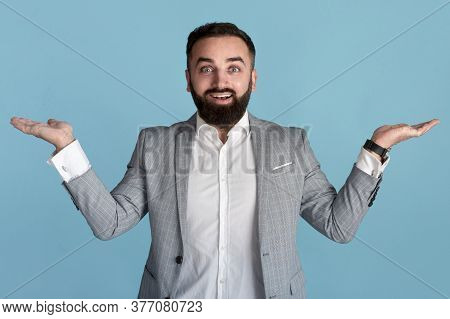 Happy Businessman Presenting Or Comparing Products, Making Scales Gesture With His Hands Over Blue B