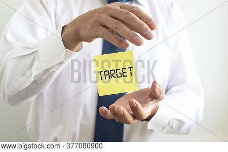 Target Word Written On Yellow Paper Note Flying Between Hands Of Businessman In Shirt And Tie. Going