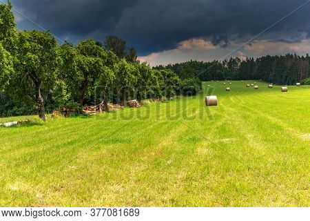 Storm Clouds In A Summer Day In The Field. Hay Harvest On The Farm. Hay Bales And Dramatic Sky. Agri