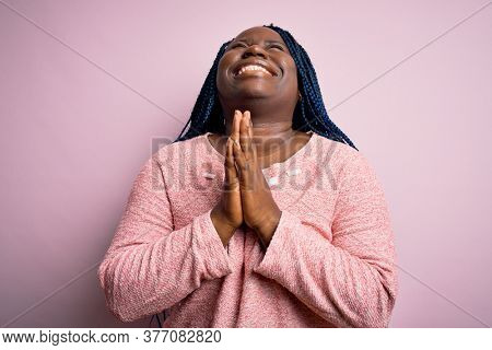 African american plus size woman with braids wearing casual sweater over pink background begging and praying with hands together with hope expression on face very emotional and worried. Begging.