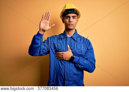 Young handsome african american worker man wearing blue uniform and security helmet Swearing with hand on chest and open palm, making a loyalty promise oath