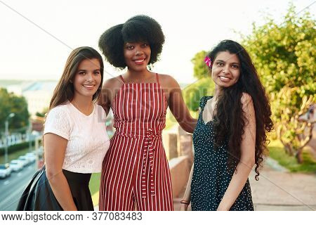 Three Beautiful Smiling Girlfriends. Multi Ethnic Group Of Women Staying Outdoors By The City Street