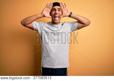 Handsome african american sportsman doing sport wearing sportswear over yellow background Smiling cheerful playing peek a boo with hands showing face. Surprised and exited