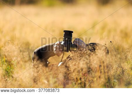 Nature Photographer In The Field With His Dslr Camera