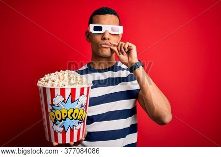Young handsome african american man watching movie using 3d glasses eating popcorns mouth and lips shut as zip with fingers. Secret and silent, taboo talking