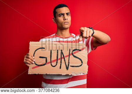 Young handsome african american man holding banner with prohibited guns message pointing with finger to the camera and to you, hand sign, positive and confident gesture from the front