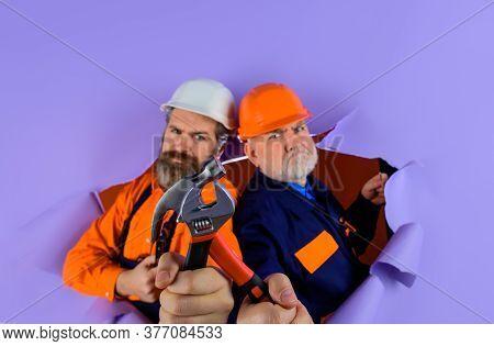 Two Repairman Working With Repair Tools. Through Paper. Advertising. Worker In Helmet. Repairman. Ha