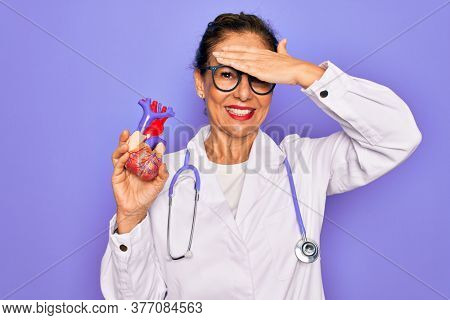 Middle age senior cardiologist doctor woman holding professional cardiology heart stressed with hand on head, shocked with shame and surprise face, angry and frustrated. Fear and upset for mistake.