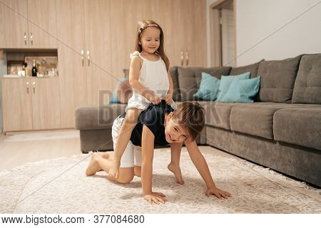 Cheerful Boy And Girl Playing At Home. Brother Carries On His Back, His Happy Sister