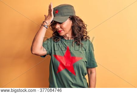 Middle age brunette woman wearing t-shirt and cap with red star symbol of communism surprised with hand on head for mistake, remember error. Forgot, bad memory concept.