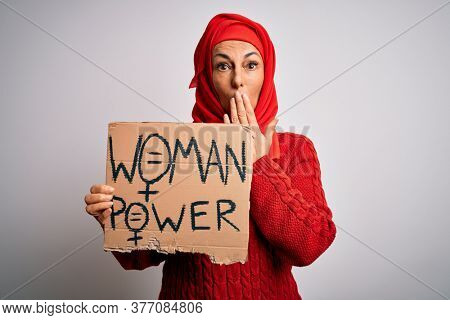 Middle age woman wearing muslim hijab asking for women rights holding banner cover mouth with hand shocked with shame for mistake, expression of fear, scared in silence, secret concept