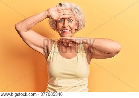 Senior grey-haired woman wearing casual clothes smiling cheerful playing peek a boo with hands showing face. surprised and exited