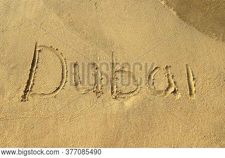 Dubai Word On Beach Sand. Dubai City Letters Is Written On A Sand. Handwriting