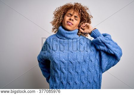 Young beautiful african american woman wearing turtleneck sweater over white background Suffering of neck ache injury, touching neck with hand, muscular pain