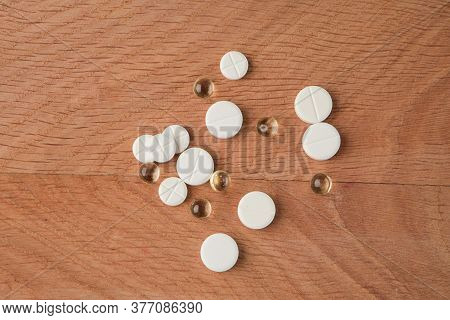 A Bunch Of Various Medicines, Pills Lying Around Without Packaging, On A Wooden Board