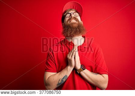 Young handsome delivery man wearing glasses and red cap over isolated background begging and praying with hands together with hope expression on face very emotional and worried. Begging.