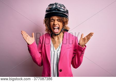 African american motorcyclist woman with curly hair wearing moto helmet over pink background celebrating mad and crazy for success with arms raised and closed eyes screaming excited. Winner concept