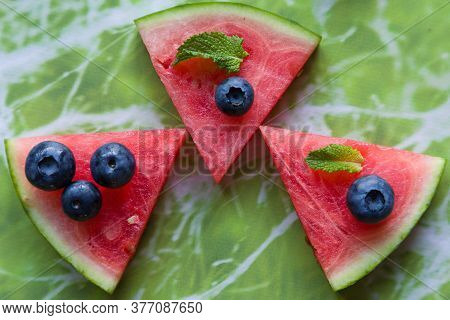 Slices Of Watermelon Covered With Red Fruit And Mint.