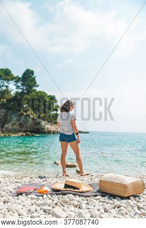 Young Pretty Woman In Summer Outfit Walking By Sea Shore Blanket With Beach Stuff On Blanket