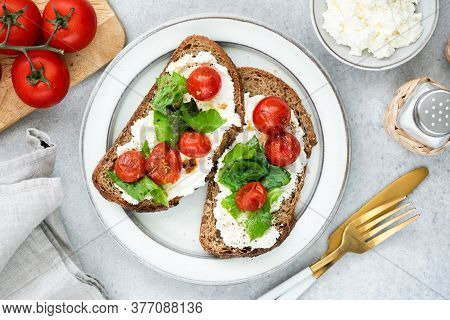Bruschetta With Ricotta Cheese, Roasted Cherry Tomatoes And Chopped Basil On A Plate. Italian Food.