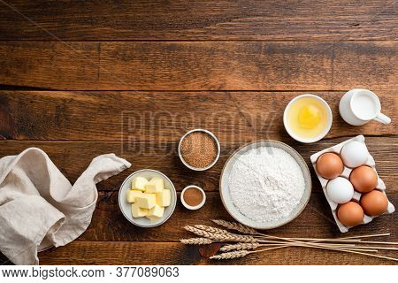 Ingredients For Baking On A Rustic Wooden Background. Flour, Eggs, Butter, Sugar And Other Ingredien